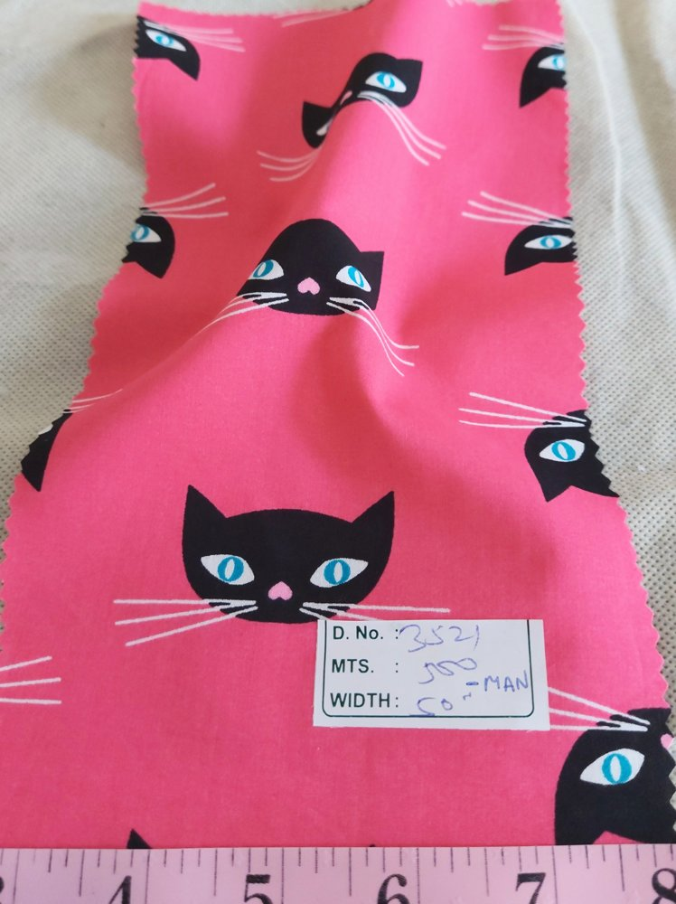 Cotton print fabric in cat print theme, with cat faces made on pink cotton, for children's clothing, quilting, sewing and dresses.