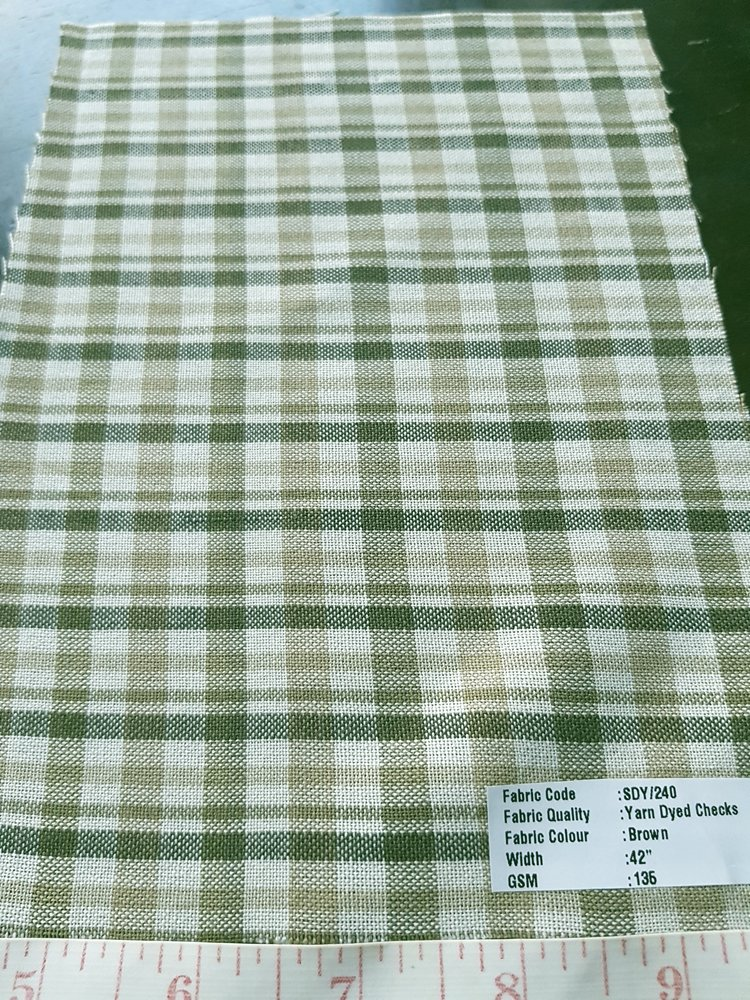 Bleeding madras fabric made by weaving yarns of several colors, in plaid patterns, with all yarns being dyed with vegetable dyes.